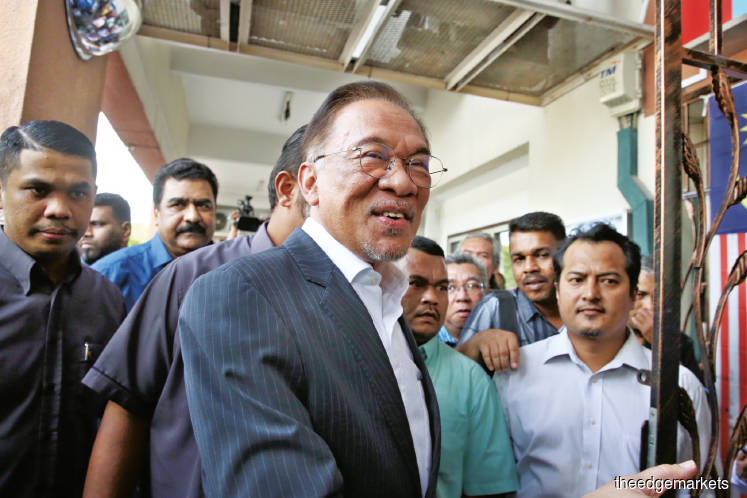 Anwar (centre) arriving at the PKR headquarters in Petaling Jaya after having an audience with the Yang di-Pertuan Agong yesterday afternoon. (Photo by Sam Fong)