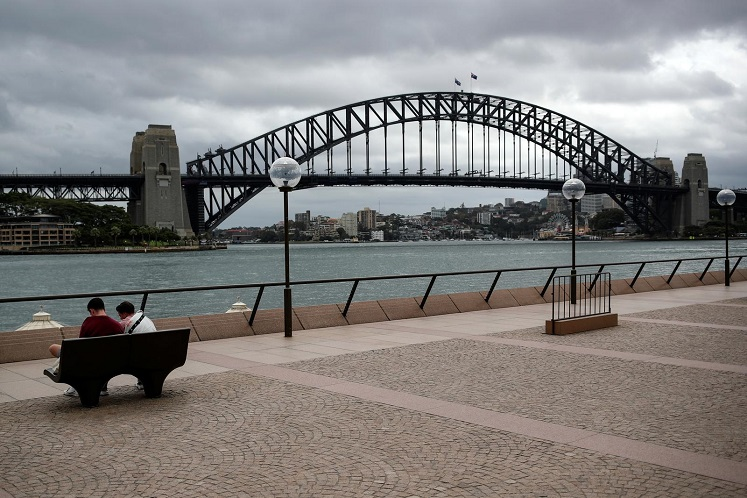 """People sit on a bench at the mostly deserted promenade of the Sydney Opera House overlooking the Sydney Harbour Bridge, in the wake of New South Wales implementing measures shutting down non-essential businesses and moving toward harsh penalties to enforce self-isolation as the spread of Covid-19 reached what the state's premier calls a """"critical stage"""" in Australia. (Photo by Reuters)"""