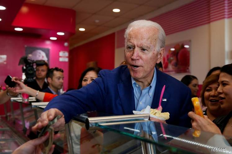 Democratic US presidential candidate and former US Vice President Joe Biden pays for ice-cream at La Michoacana during the state's Super Tuesday Democratic presidential primary election in Los Angeles, California, US, on March 3, 2020. (Photo by Reuters)