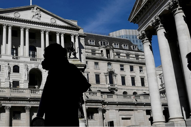 People wearing masks walk past the Bank of England, as the spread of Covid-19 continues, in London, Britain, March 23, 2020. (Photo by Reuters)