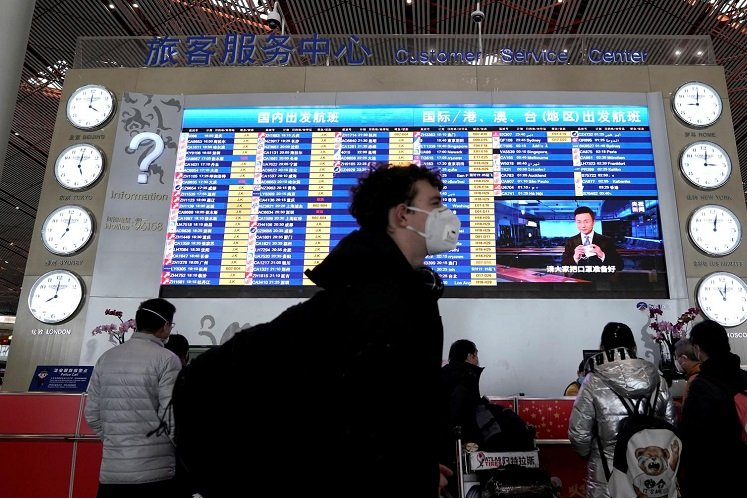 A foreign traveller wearing a mask walks past a departures information board at Beijing Capital International Airport in Beijing, China as the country is hit by an outbreak of the new coronavirus, Feb 1, 2020. (Photo by Reuters)