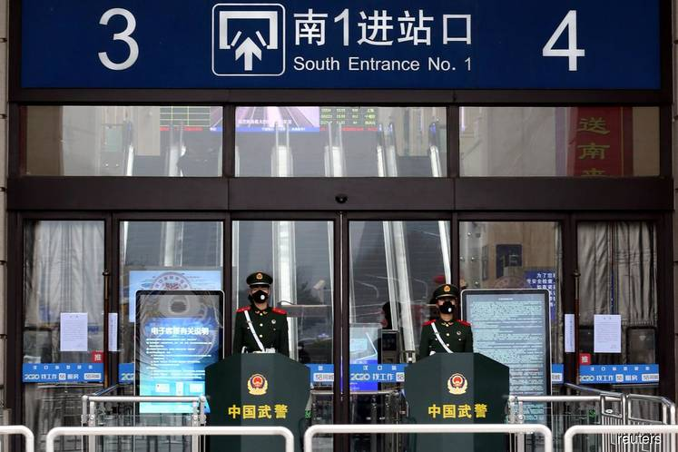 China parliamentary officers wearing masks stand guard at an entrance of the closed Hankou Railway Station after the city was locked down following the outbreak of a new coronavirus in Wuhan, Hubei province, China, Jan 23. (Photo by Reuters)