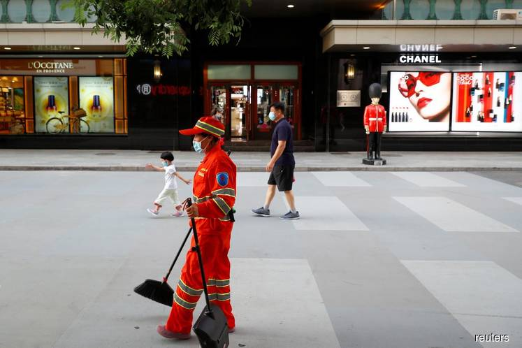 People walk past a department store of the Wangfuijing Group in Beijing, China. (Photo by Reuters)