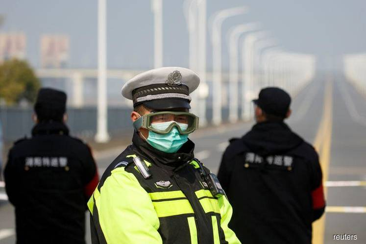 A police officer wears a face mask and goggles at a checkpoint at the Jiujiang Yangtze River Bridge as the country is hit by an outbreak of the novel coronavirus in Jiujiang, Jiangxi province, China, Feb 4, 2020. (Photo by Reuters)