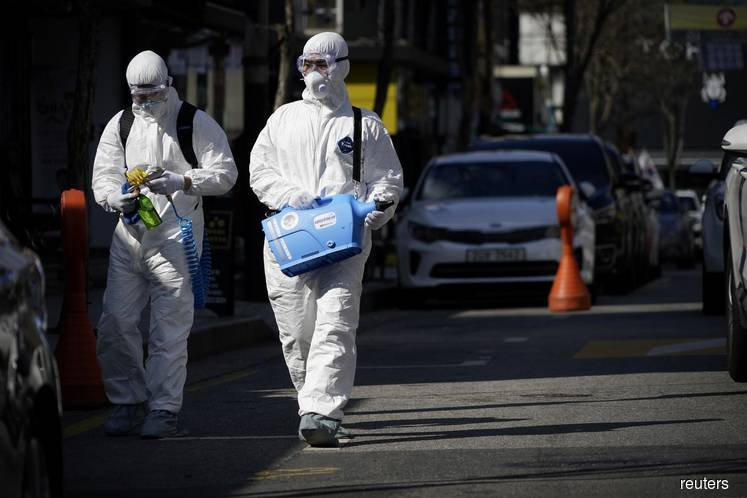 Employees from a disinfection service company sanitize a shopping district in Seoul, South Korea, on Feb 27, 2020. (Photo by Reuters)