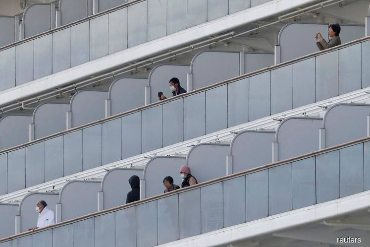 Passengers, some wearing face masks, are seen on the cruise ship Diamond Princess, where 10 more people were tested positive for coronavirus on Thursday, at Daikoku Pier Cruise Terminal in Yokohama, south of Tokyo, Japan, Feb 7, 2020. (Photo by Reuters)