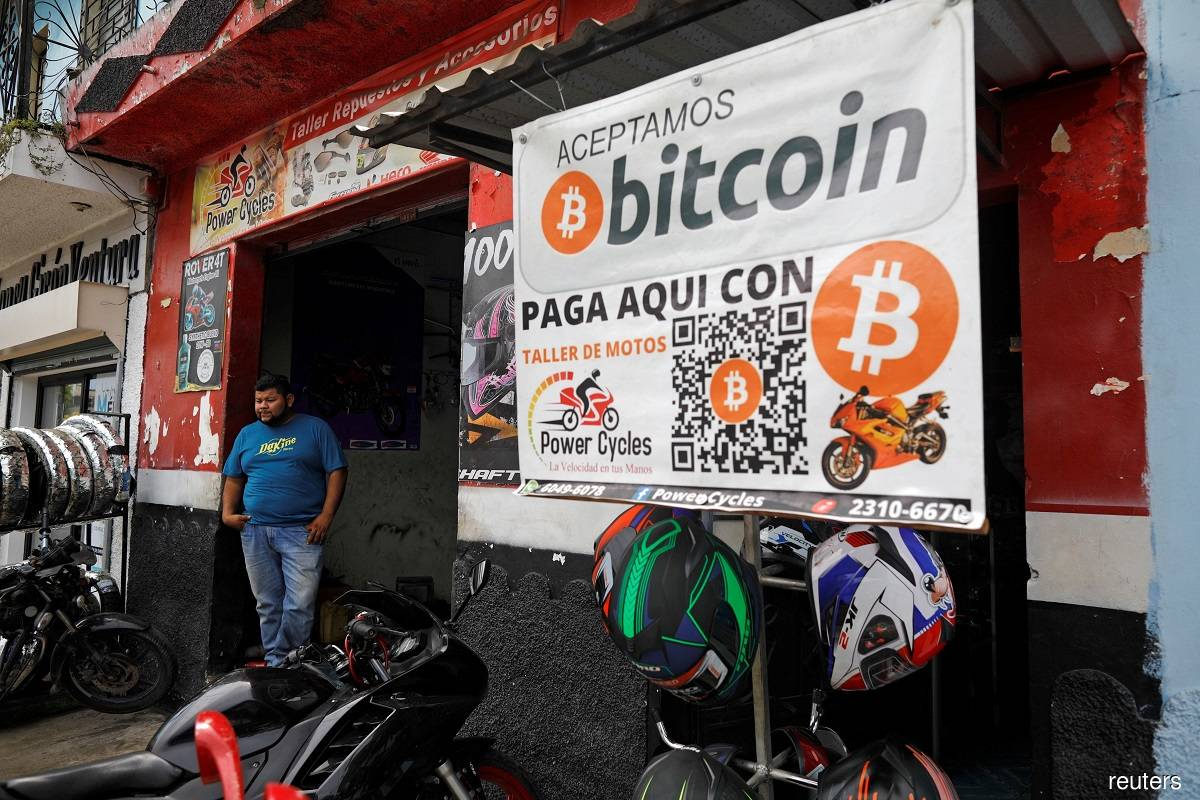 """A sign that says """"Bitcoin accepted here"""" on display in front of a motorcycle repair shop in Aguilares, El Salvador."""
