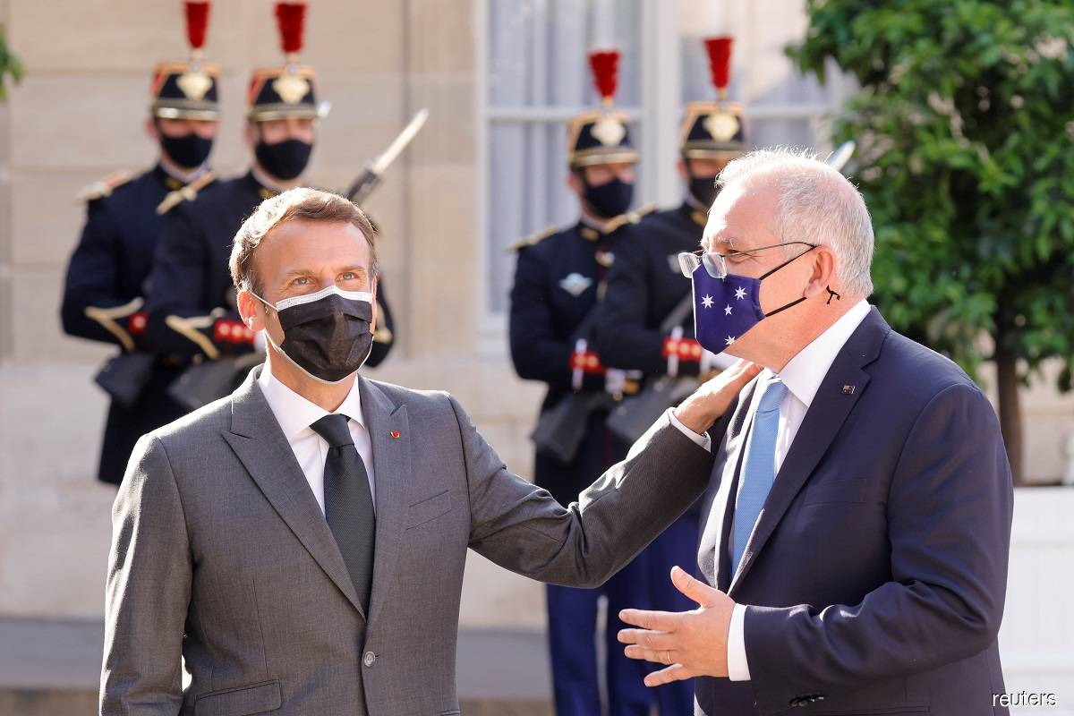 French President Emmanuel Macron (left) welcoming Australian Prime Minister Scott Morrison (right) in front of the Elysee Palace in Paris, France on June 15, 2021, shortly after a meeting of G7 leaders in Britain.