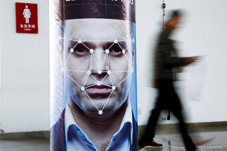 FILE PHOTO: A man walks past a poster simulating facial recognition software at the Security China 2018 exhibition on public safety and security in Beijing, China Oct 24, 2018. (Photo credit: Thomas Peter/REUTERS)