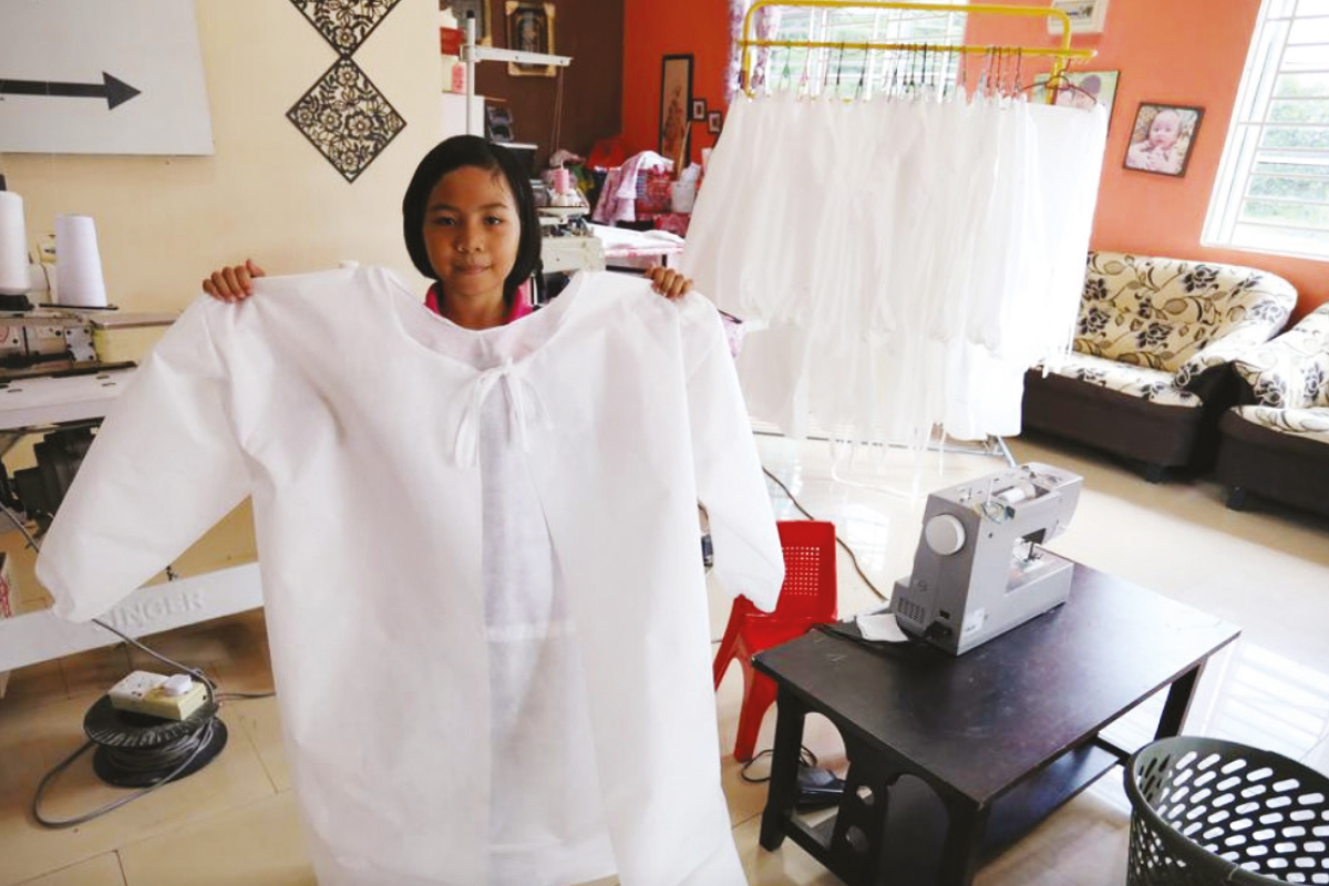 Nur Afia with some of the personal protective equipment gowns she sewed for frontliners in the early months of the pandemic. (Photo by Reuters)