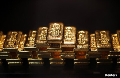 Gold falls on hawkish comments by Fed officials, dollar pressure