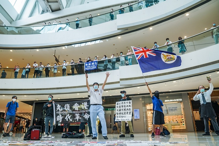 A demonstrator waves a colonial-era Hong Kong flag during a protest at the IFC shopping mall in Hong Kong on May 29. (Photo by Bloomberg)