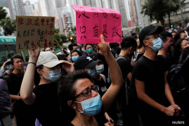 Dozens of Hong Kong protesters appear in court on rioting charges