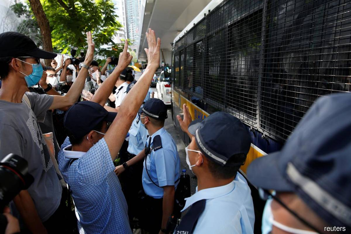 Supporters of Tong Ying-kit, the first person charged under the new national security law, greet a prison van outside West Kowloon Magistrates' Courts in Hong Kong, China, July 6, 2020.