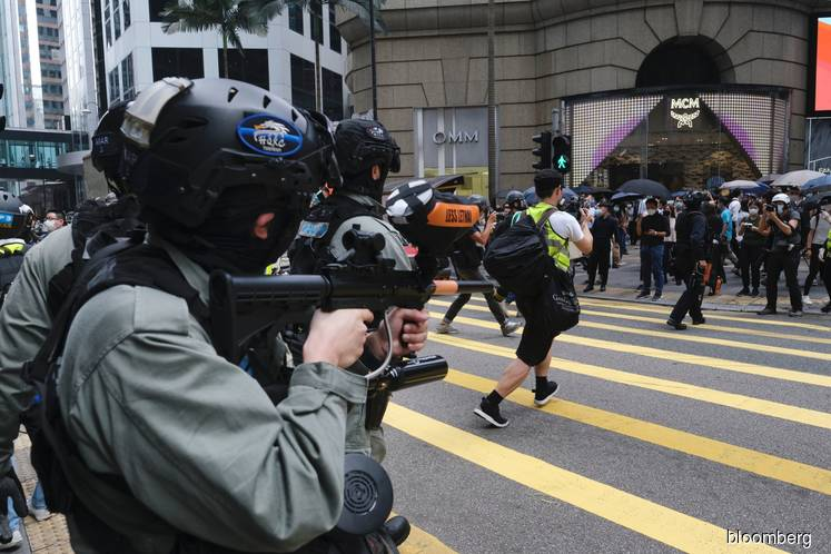 A riot police officer aiming his pepper-pellet rifle at protesters in the Central district of Hong Kong, China today.