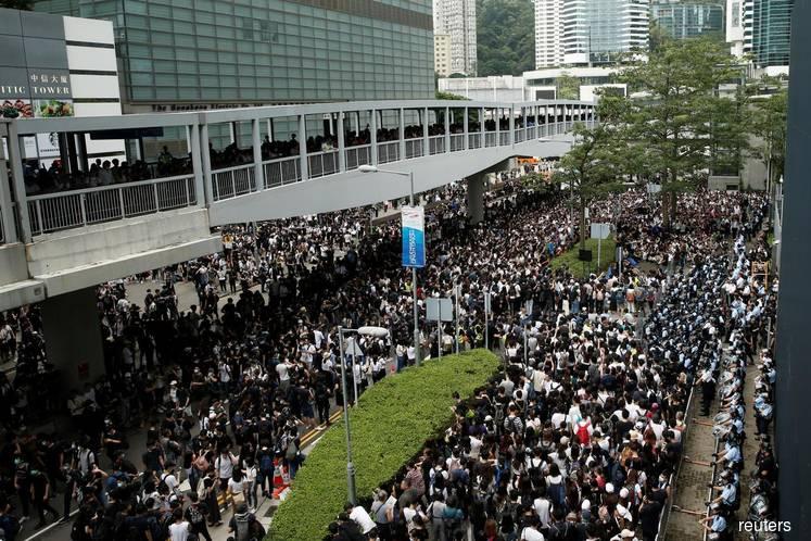 Hong Kong protests send stocks lower, spark scramble for cash