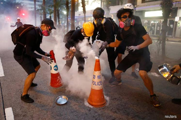 Protesters blockade universities, stockpile makeshift weapons as chaos grips Hong Kong