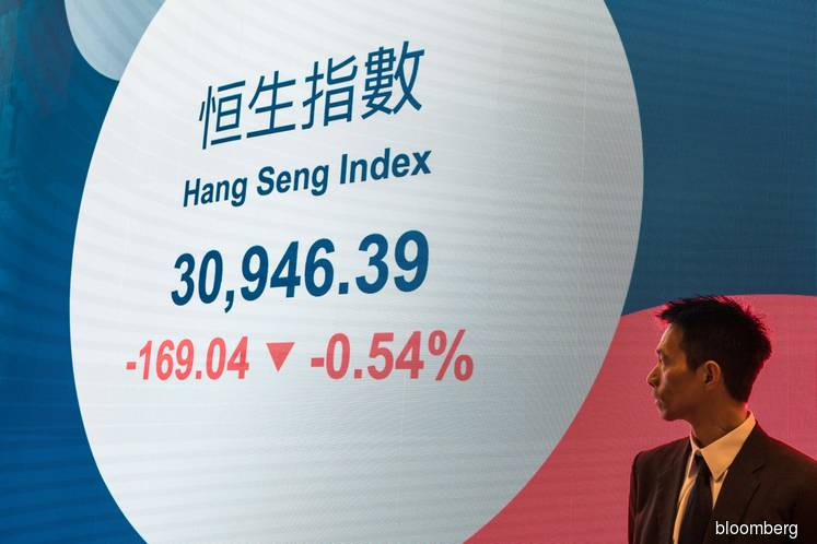 Hong Kong stocks swing wildly as China approves security law