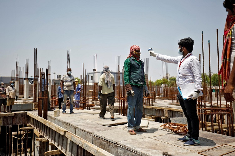 File picture of a health worker using an infrared thermometer to measure the temperature of a labourer at a construction site in the Indian city of Ahmedabad to guard against Covid-19 on April 30, 2020. (Photo by Reuters)