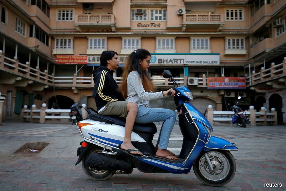 Girls ride an electric scooter in Ahmedabad, India, December 30, 2018. Picture taken December 30, 2018.