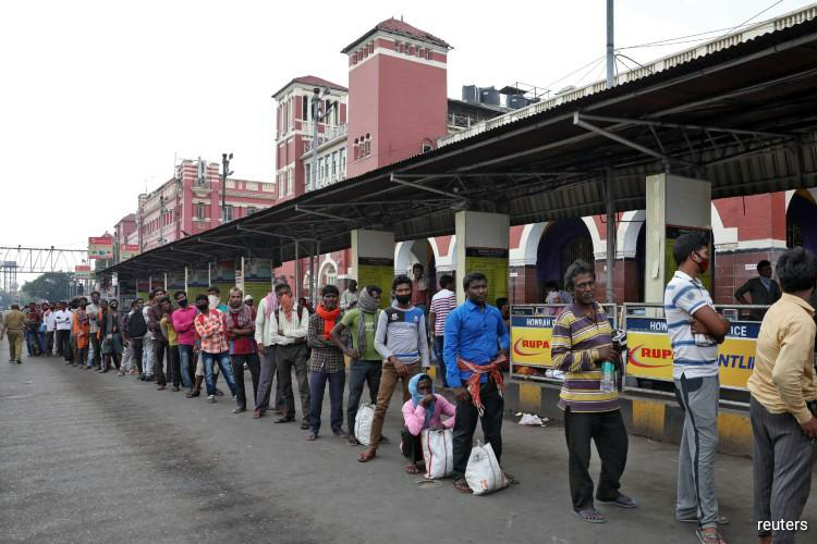 Migrant workers wait in a queue to receive free food outside Howrah railway station after India ordered a 21-day nationwide lockdown to limit the spreading of Coronavirus disease (COVID-19), in Kolkata, India, March 25, 2020. (Photo by Reuters)