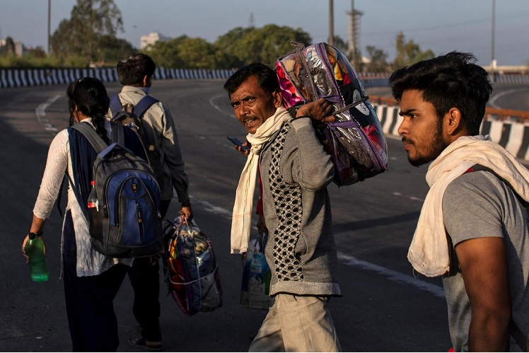 A migrant worker and his family walk along a road as they return to their village, during a 21-day nationwide lockdown to limit the spreading of Covid-19, in New Delhi, India. (Photo by Reuters)