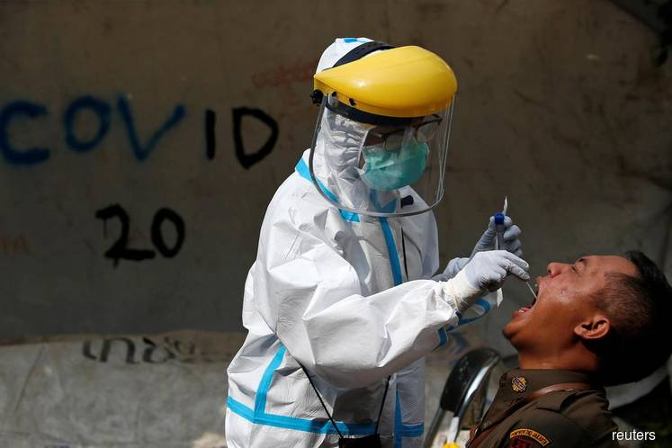 A healthcare worker in protective gear collects a swab sample to be tested for Covid-19 from a civil servant at a traditional textile market in Jakarta, Indonesia. (Photo by Reuters)
