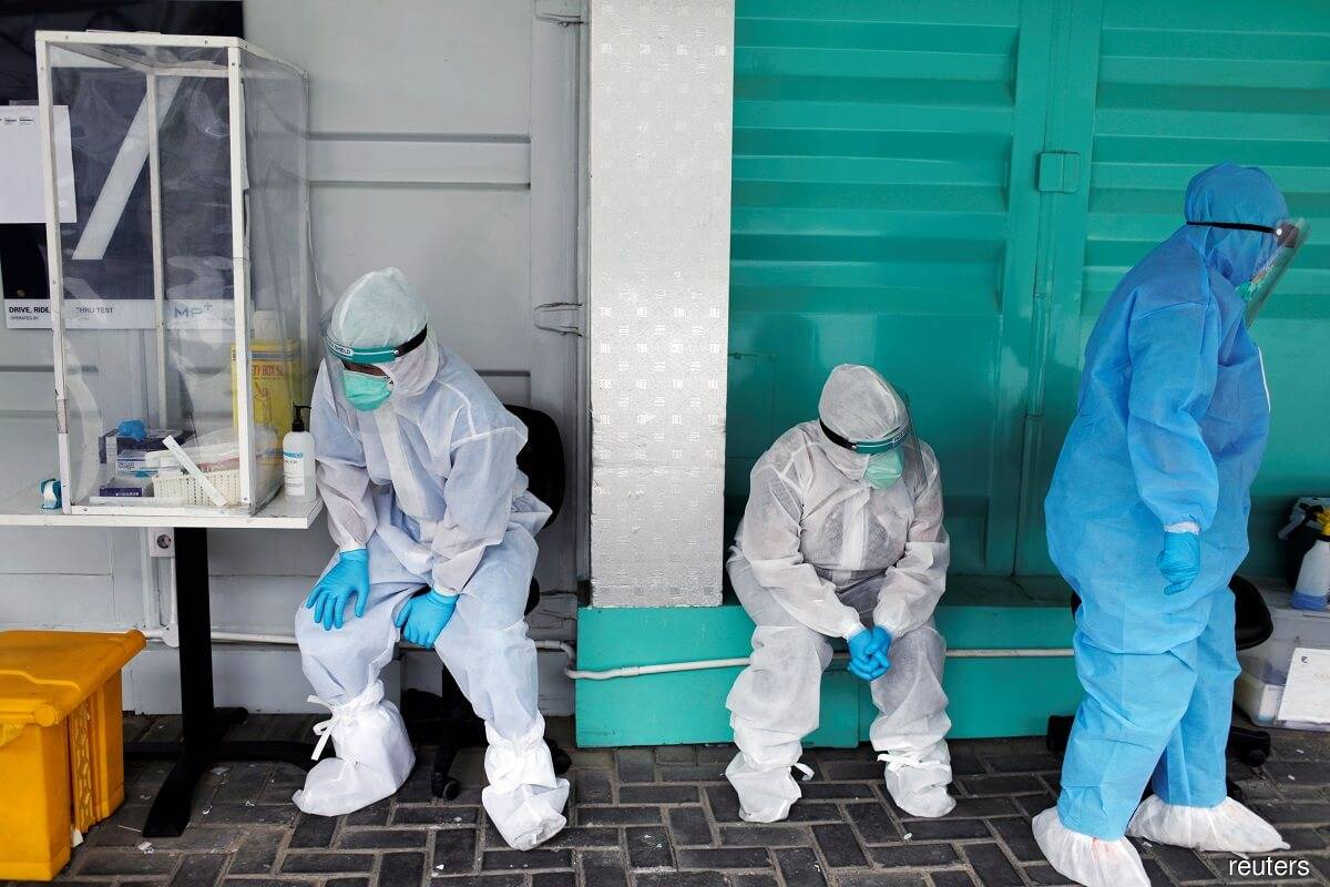 Medical workers wearing personal protective equipment take a break while collecting swab samples to be tested for Covid-19, at Genomik Solidaritas Indonesia lab, as the outbreak continues in Jakarta, Indonesia, Sept 29, 2020. (Photo by Reuters)
