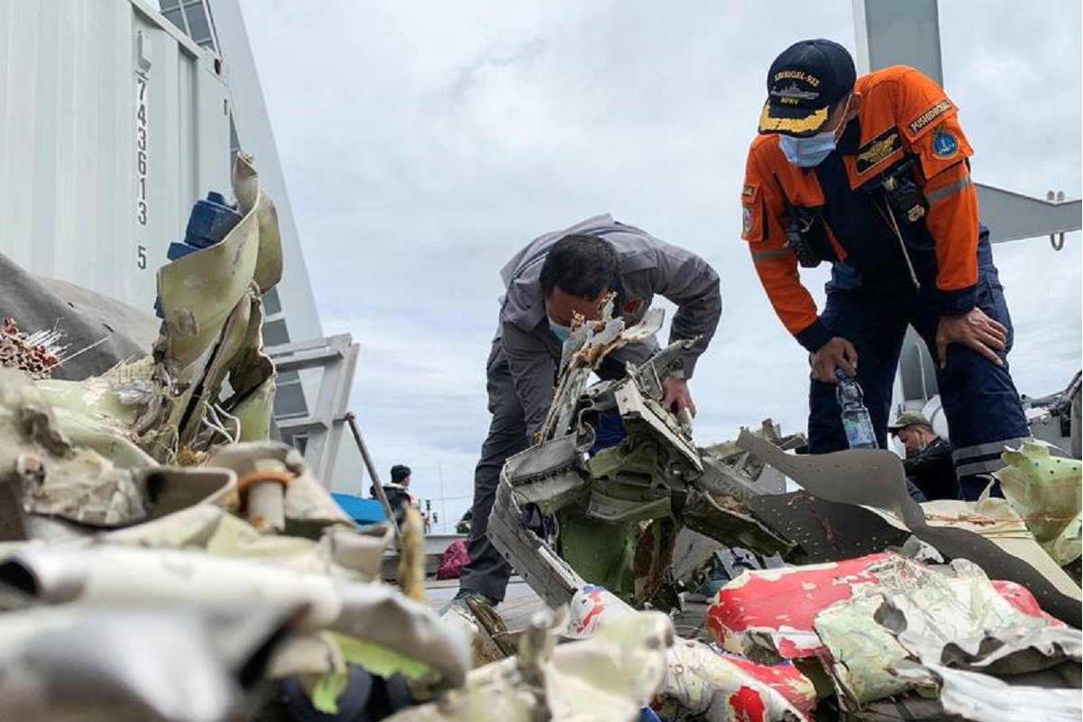 A National Transportation Safety Committee official (left) and a search and rescue agency member on board the navy ship KRI Rigel inspect debris retrieved from the sea floor during the search and rescue operation for Sriwijaya Air flight SJ 182 off the Jakarta coast, Indonesia, Jan 12, 2021. (Photo by Reuters)