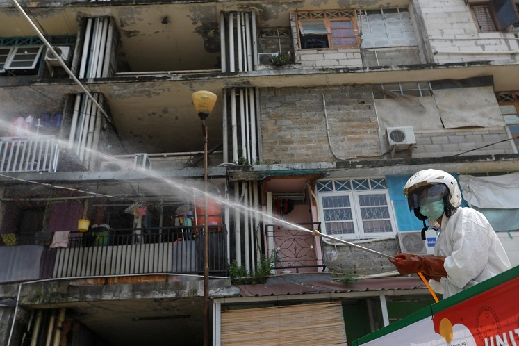 A Red Cross personnel wearing a protective suit sprays disinfectant in a densely populated neighbourhood area, amid the spread of Covid-19 in Jakarta, Indonesia, April 4, 2020. (Photo by Reuters)