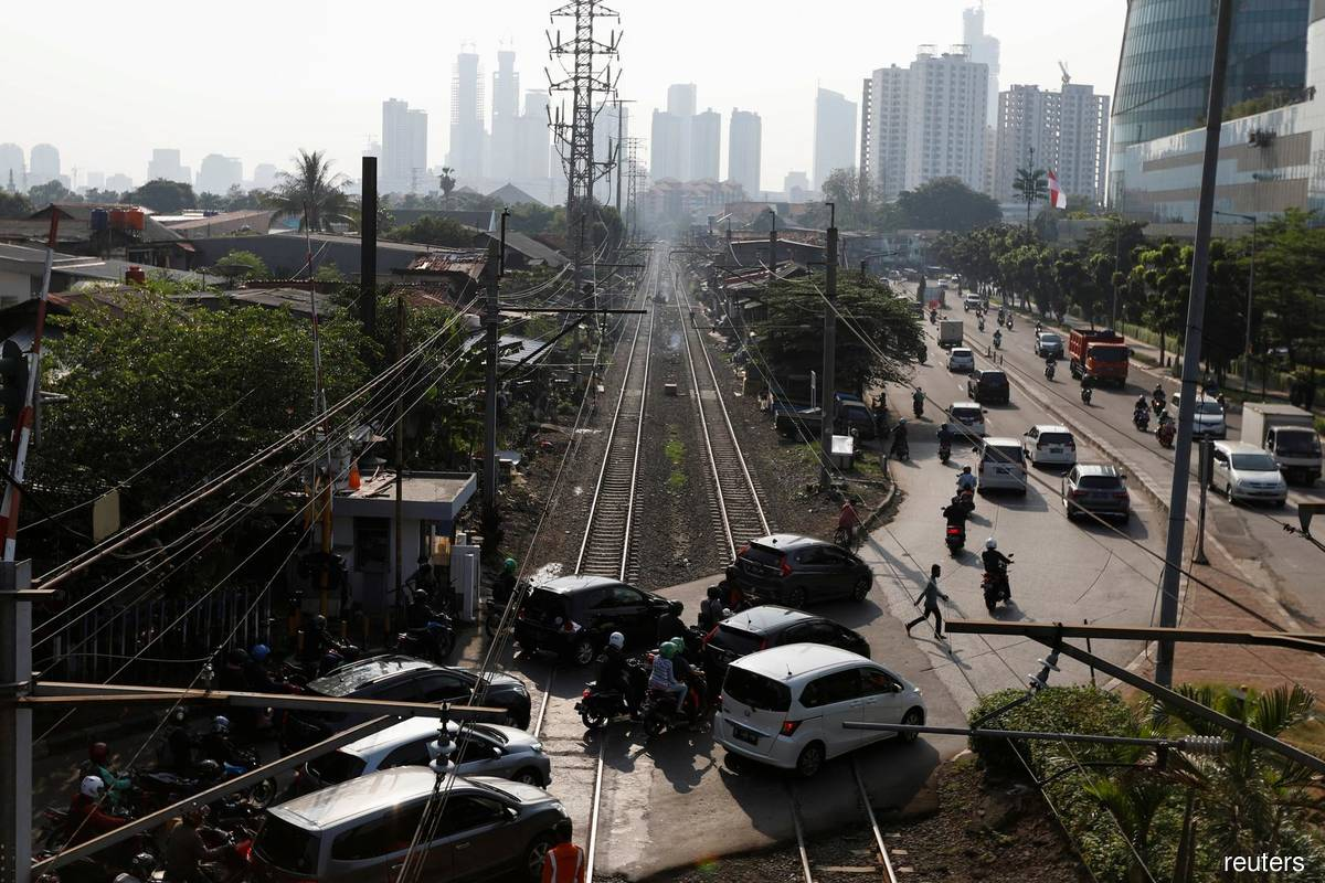 A man crosses a road during morning rush hours after the government eased restrictions following the Covid-19 outbreak, near a densely populated residential area in Jakarta, Indonesia, July 8, 2020. (Photo by Reuters)
