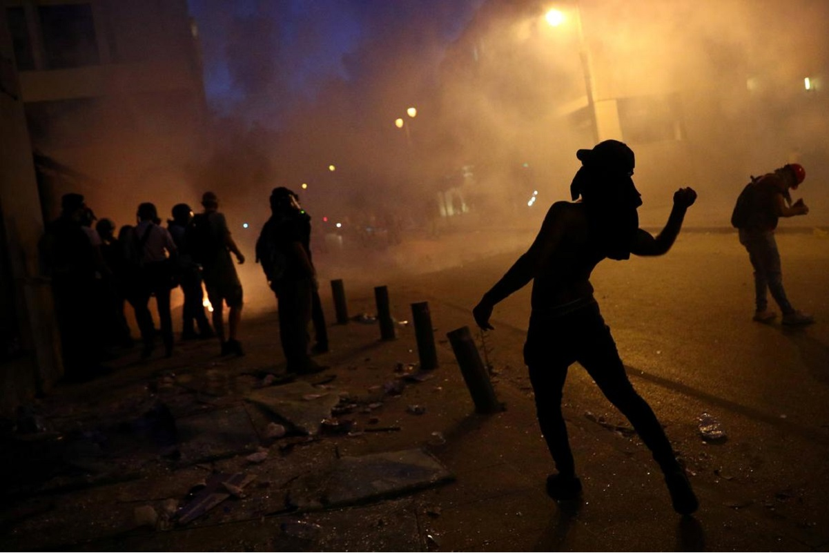 A demonstrator throws a rock during a protest following Tuesday's blast, in Beirut, Lebanon.