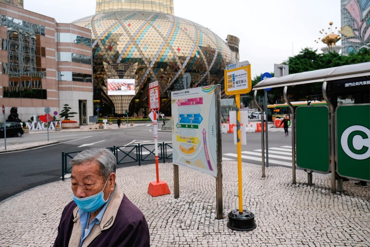 A man wears a mask as he walks in front of the closed Grand Lisboa casino, following the Covid-19 outbreak, in Macau, China.
