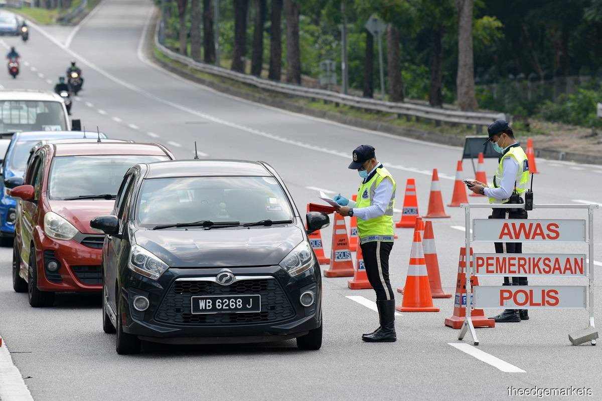 Police checking validity of commuters' travel documents before letting them pass at a roadblock on June 8, 2021 amid the Movement Control Order period. (Photo by Suhaimi Yusuf/The Edge)
