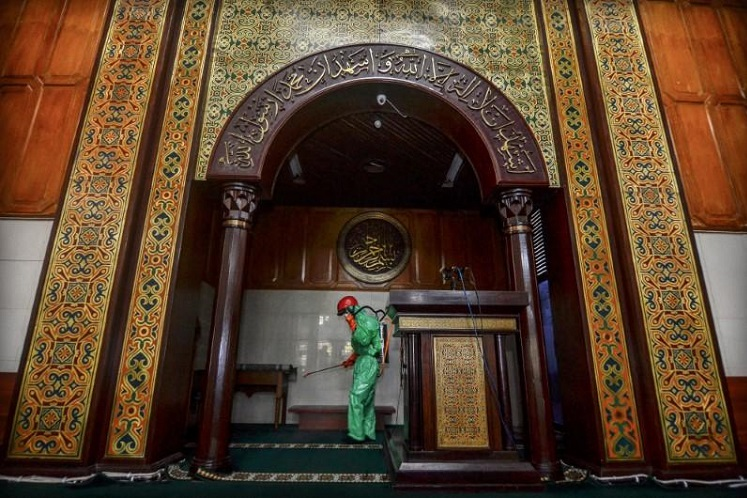 Medical officer sprays disinfectant in mosque amid the coronavirus disease (Covid-19) outbreak in Tasikmalaya, West Java, Indonesia, March 18, 2020 in this photo taken by Antara Foto. (Antara Foto/Adeng Bustomi/via Reuters)