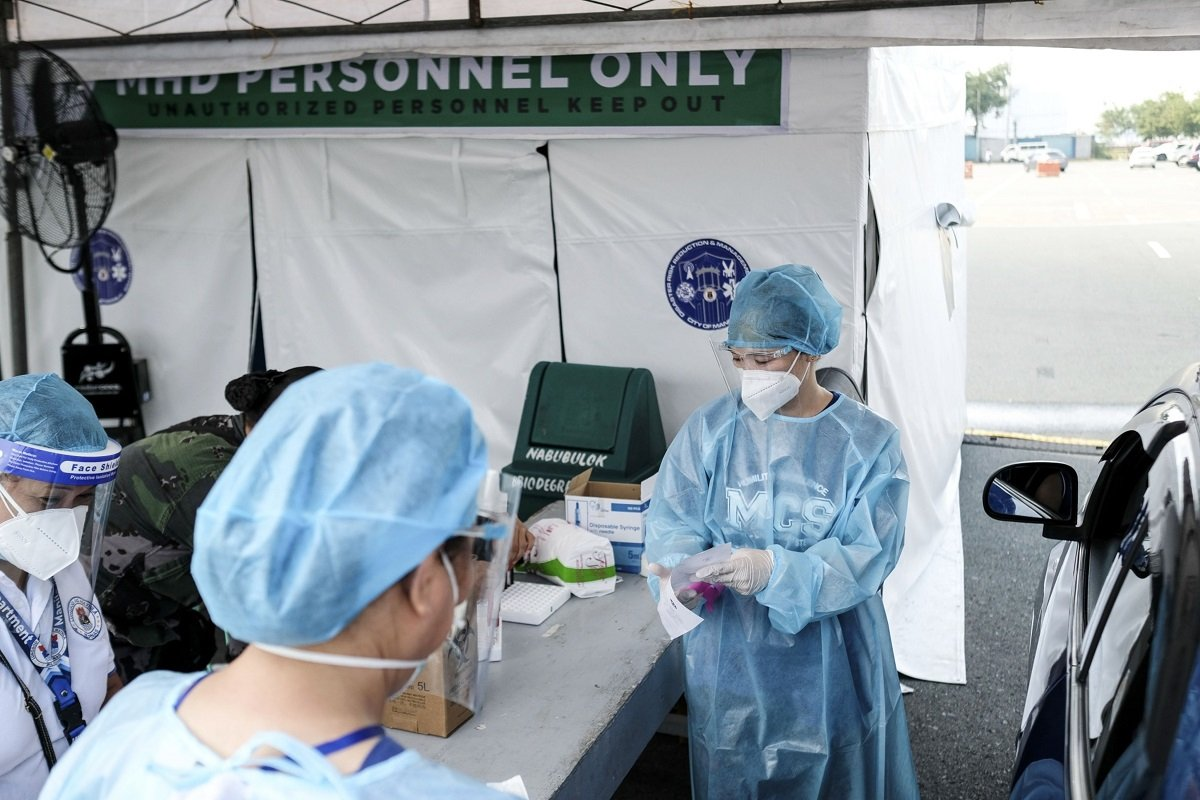 Health workers work at a drive-in Covid-19 testing site set up at the Quirino Grandstand in Manila, the Philippines, on July 21.