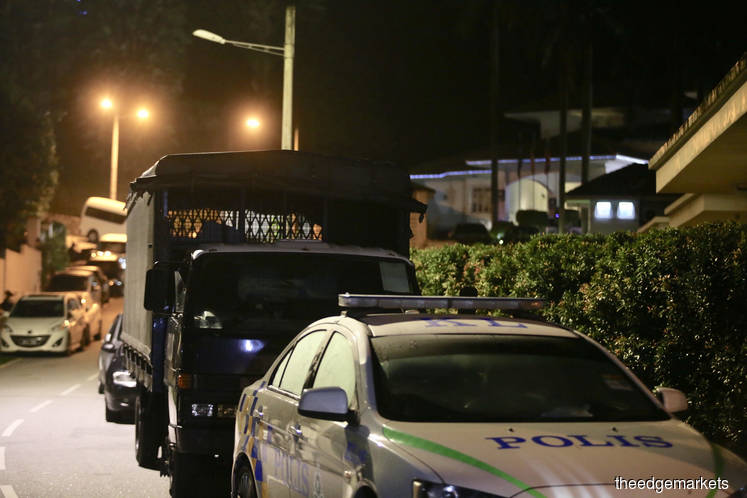 Police cars and Black Maria parked outside Najib's house