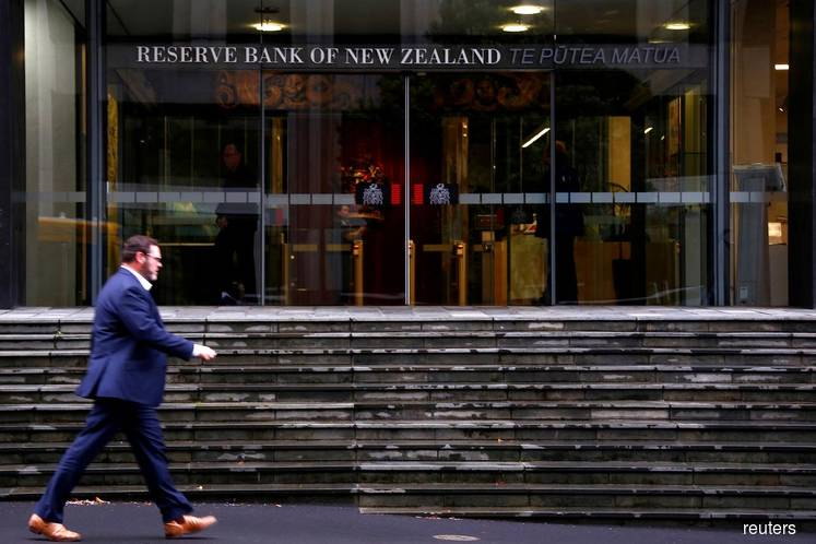 NZ central bank stands pat, flags more easing to combat risks to growth