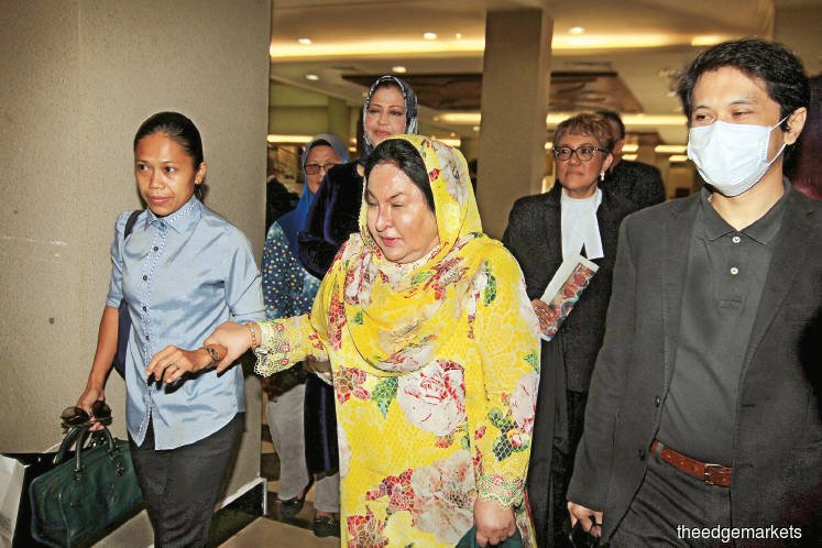 Rosmah (right) assisted by an aide arriving for her trial. (Photo by Shahrin Yahya)