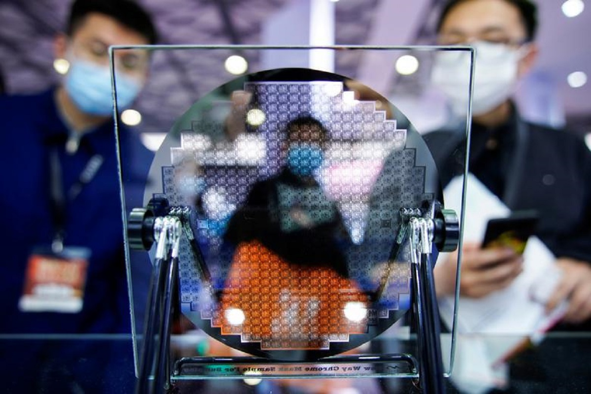Visitors look at a display of a semiconductor device at Semicon China, a trade fair for semiconductor technology, in Shanghai, China, March 17, 2021. (Photo by Reuters)