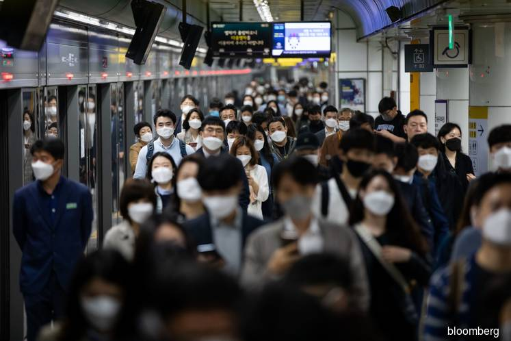 Passengers with protective masks walking through the subway station in Seoul, South Korea.