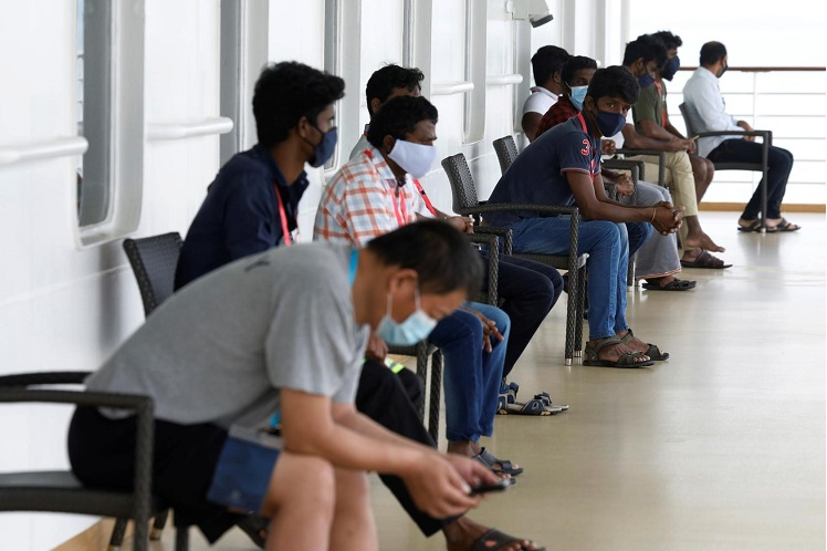 Migrant workers sit at a designated outdoor area onboard the SuperStar Gemini cruise ship which is being used as a temporary accommodation facility for migrant workers who had recovered from Covid-19, amid the Covid-19 outbreak in Singapore, May 23, 2020. (Photo by Reuters)