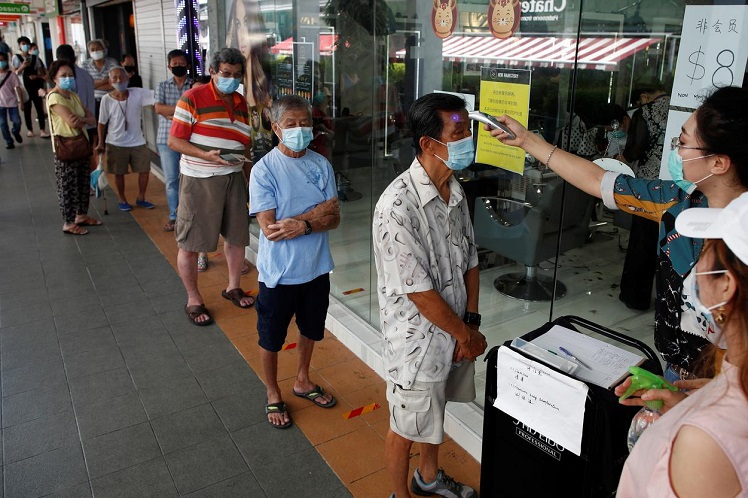 Customers queue up to have their temperature taken outside a hairdressing salon as they reopen for business amid the Covid-19 outbreak in Singapore, May 12, 2020. (Photo by Reuters)