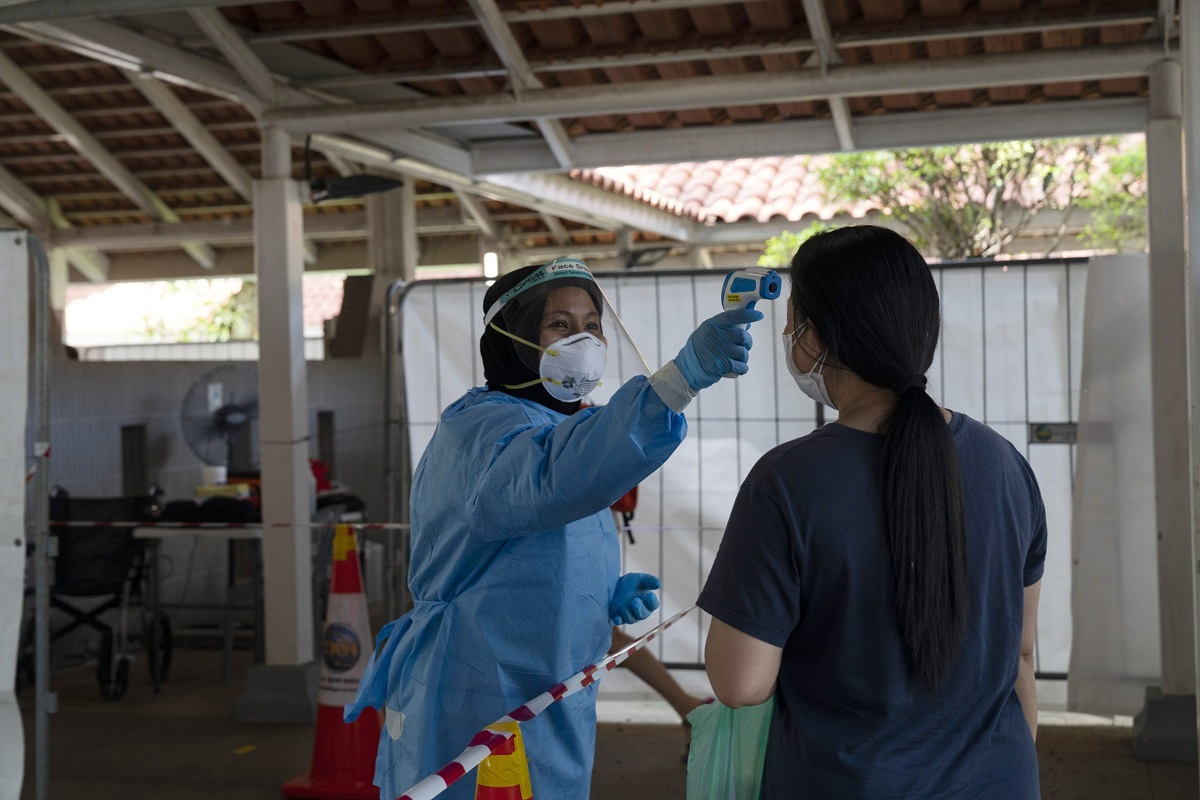 A health worker checks the temperature of a resident at a Covid-19 test site set up at a Housing & Development Board (HDB) public housing estate in the Ang Mo Kio area of Singapore, on Sunday, July 25, 2021. (Photo by Bloomberg)