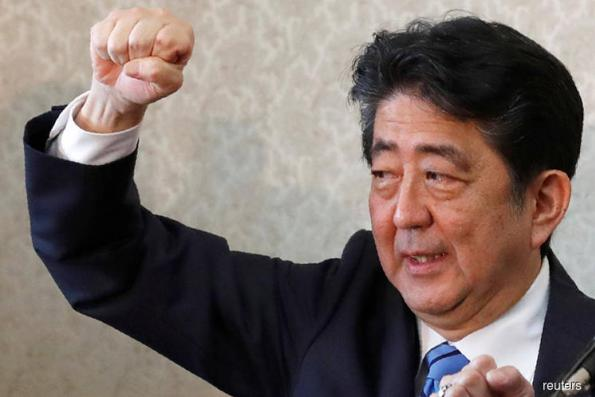 Japan PM Abe keeps key ministers in posts, taps one woman for cabinet