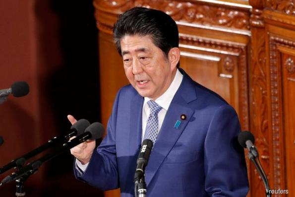 Japan's Abe sets sights on more foreign workers, higher sales tax