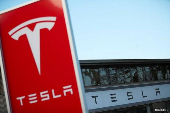 Tesla shares dive again, stung by fatal crash, credit downgrade