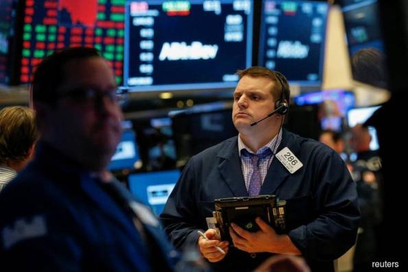 Wall St hit by weak industrial earnings, hawkish Fed