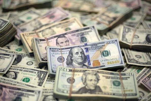 Dollar holds onto gains as trade tensions linger