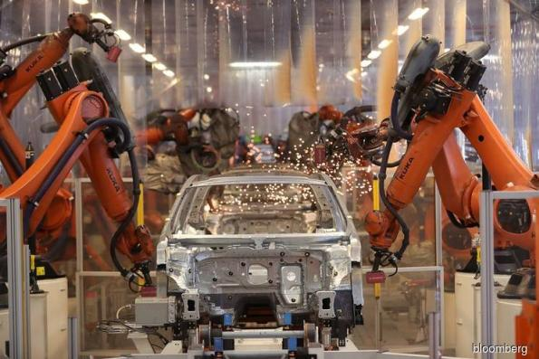 In a World of Robots, Carmakers Persist in Hiring More Humans